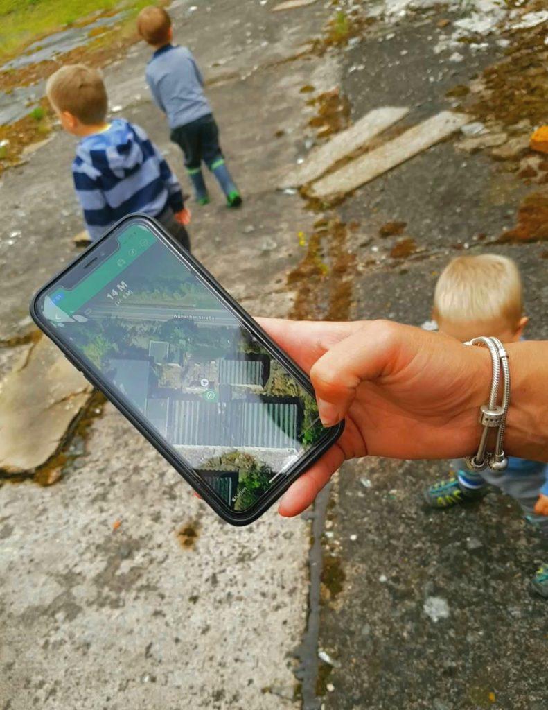 Geocachen im Geiseltalsee, Blick auf das Handy, kinder im Hintergrund