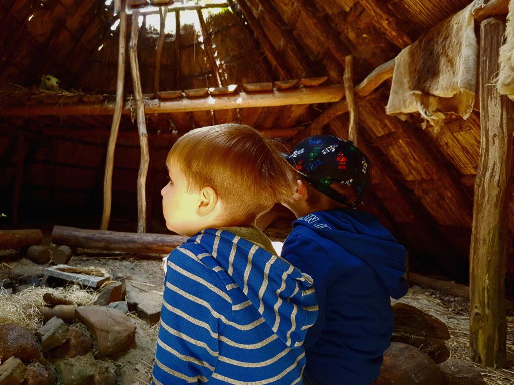Kinder sitzen in einer Steinzeithütte an der Lagerfeuerstelle