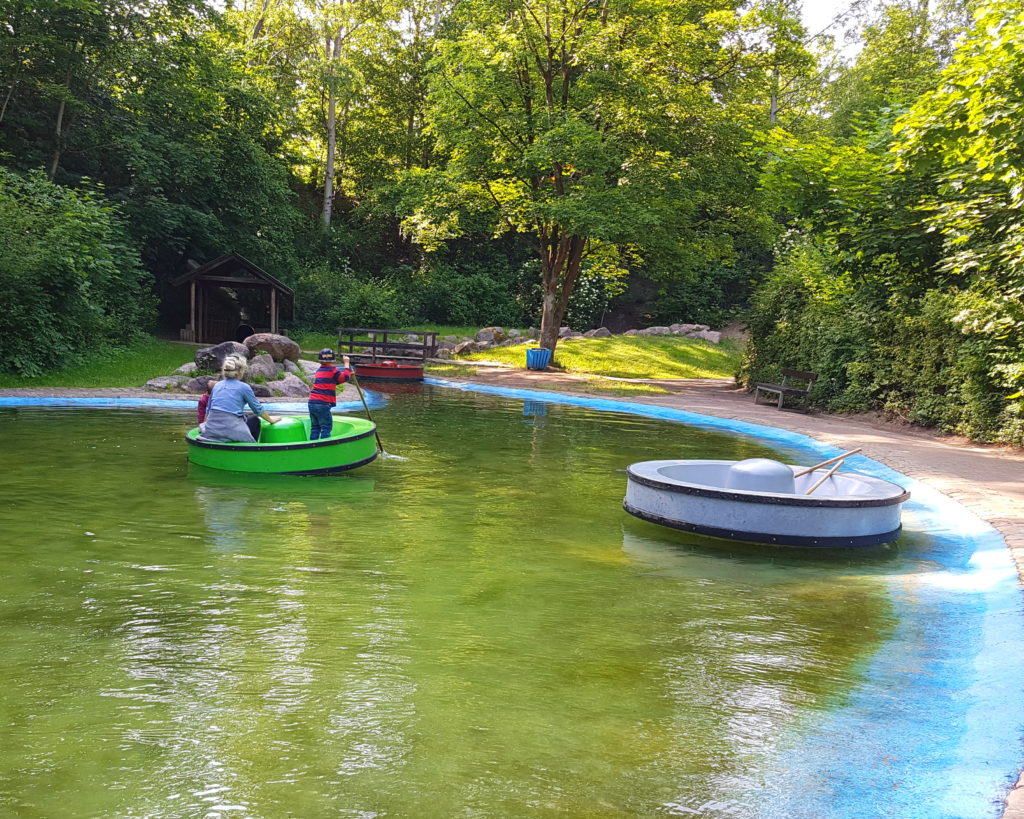 Die Kinder fahren auf dem Floß im Spielpark an der Wingst, im Hintergrund ist das Ende der riesigen Tunnelrutsche zu sehen