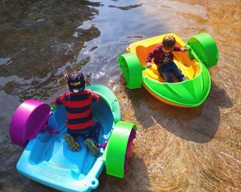 Die Kinder fahren auf dem Wasser mit kleinen Booten