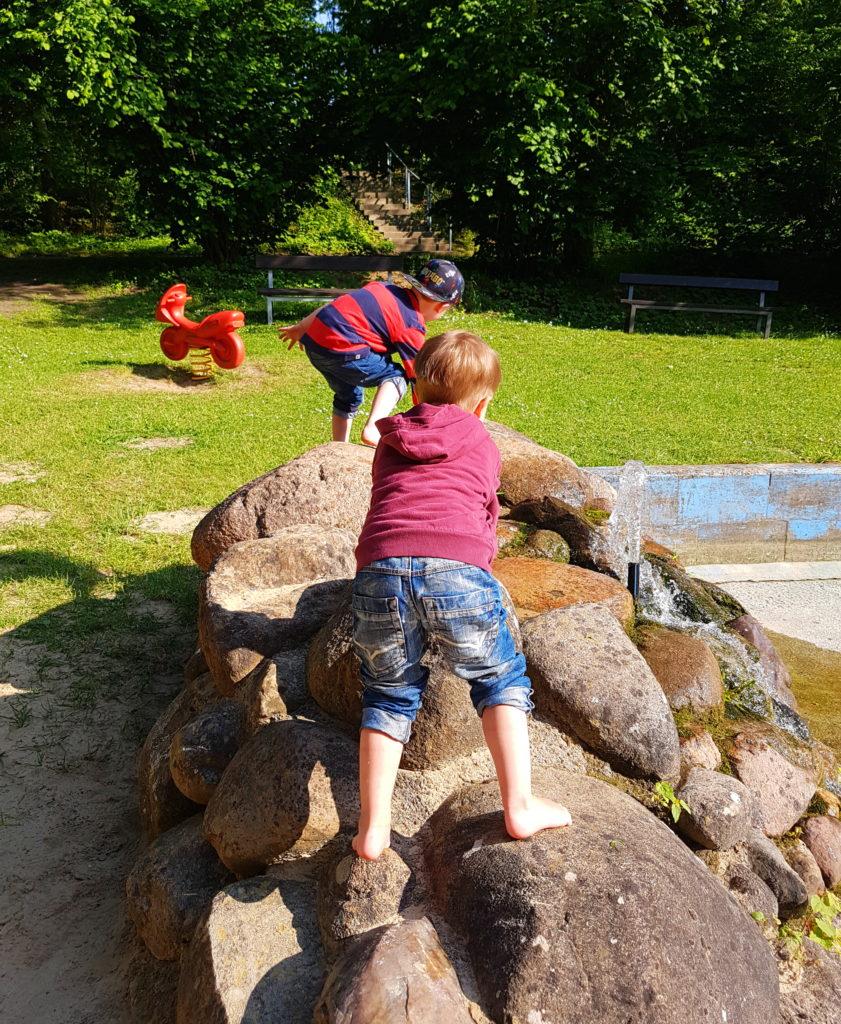 Die Kinder klettern auf den Steinen am Wasserbecken