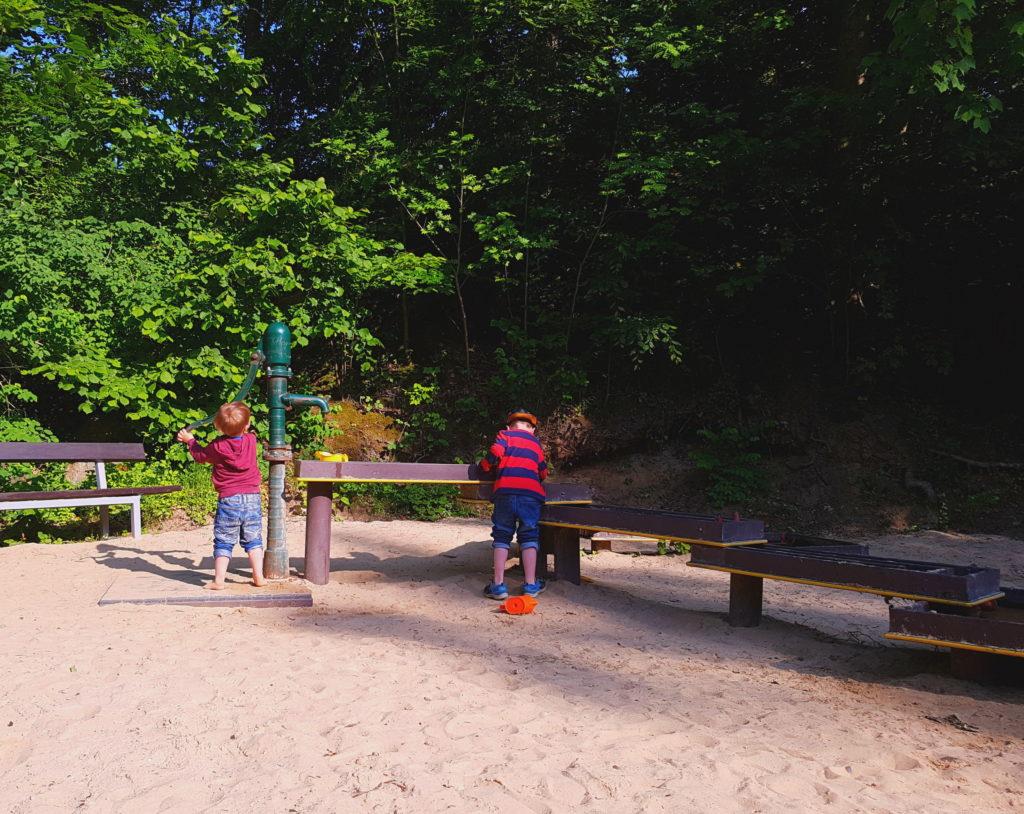 Die Kinder pumpen Wasser an der Goldwaschanlage im Spielpark