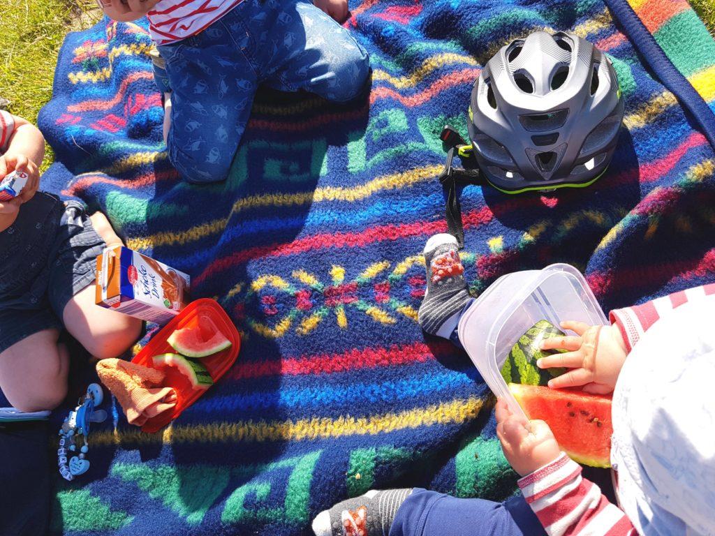 Kinder Picknick auf der Decke im Grünen mit Melone