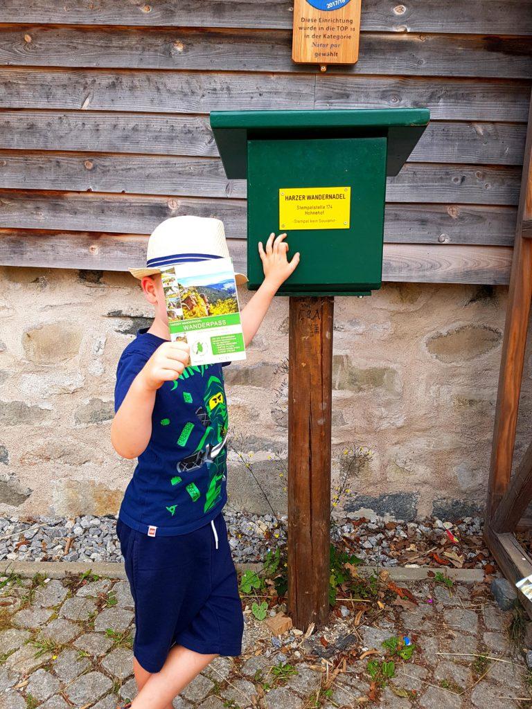 Junge am Stempelkasten Harzer Wandernadel Hohnehof Löwenzahn Entdeckerpfad