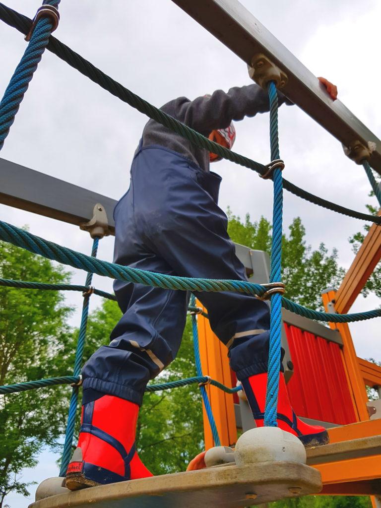 Junge in Regensachen auf dem Spielplatz