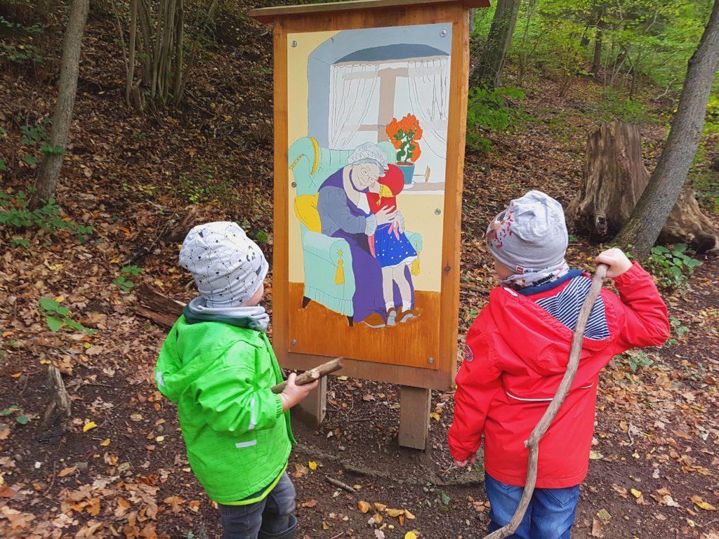 märchenweg im Harz, kinder stehen vor einem Bild im Wald