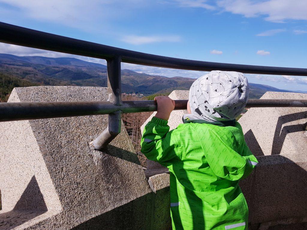 Kind genießt die Aussicht vom Bilsmarkturm auf dem Wernigeröder Märchenweg im Harz, Blick auf den Brocken