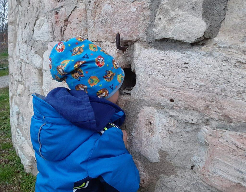 Kind schaut durch ein Loch am Burgfried (Dicker Wilhelm) am Schloss Neuenburg in Freyburg, Lockdown Ausflüge für Kinder