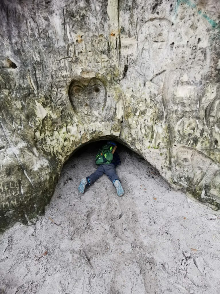 Sandsteinhöhlen erkunden. Nur noch die Beine schauen aus der kleinen Sandsteinhöhle raus.