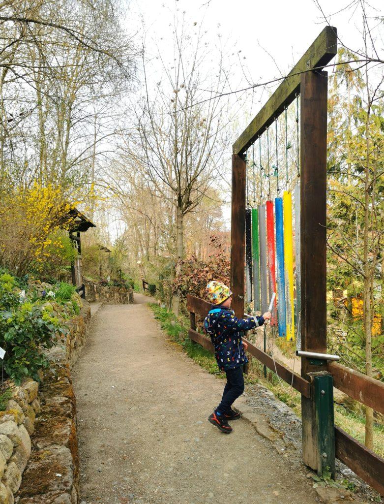 Kind an den Klangstäben auf dem Naturlehrpfad im Heimatnaturgarten Tierpark Weißenfels