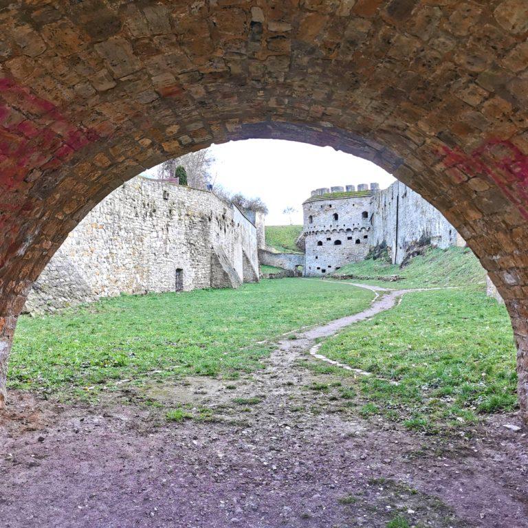 Blick durch den Rundbogen einer Brücke auf die Burg Querfurt